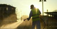 Рабочий дезинфицирует улицу из-за вспышки коронавируса в Италии