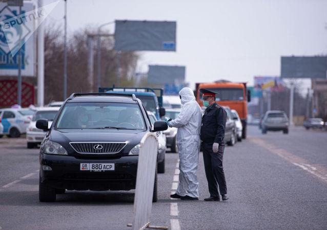 Медсотрудник проверяет температуру водителя на санитарно-карантинном блокпосту на въезде в город Бишкек. Архивное фото