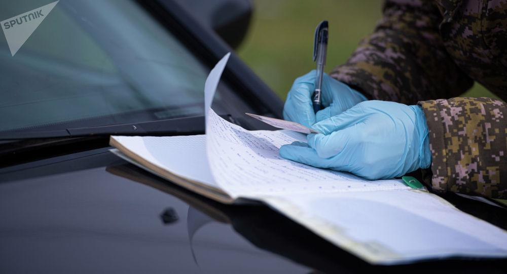 Милиция кызматкери айдоочулук күбөлүктүн маалыматын толтурууда. Архивдик сүрөт