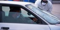 Медсотрудник проверяет температуру водителя на санитарно-карантинном блокпосту