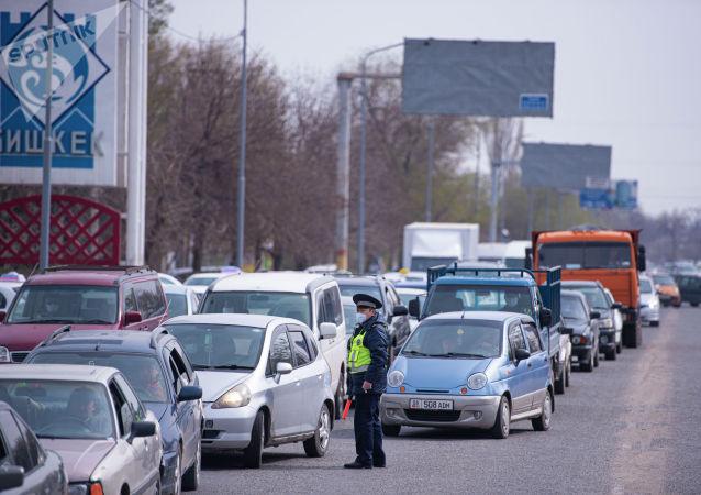 Сотрудник патрульной милиции регулирует движение автомобилей на санитарно-карантинном посту на въезде в город Бишкек