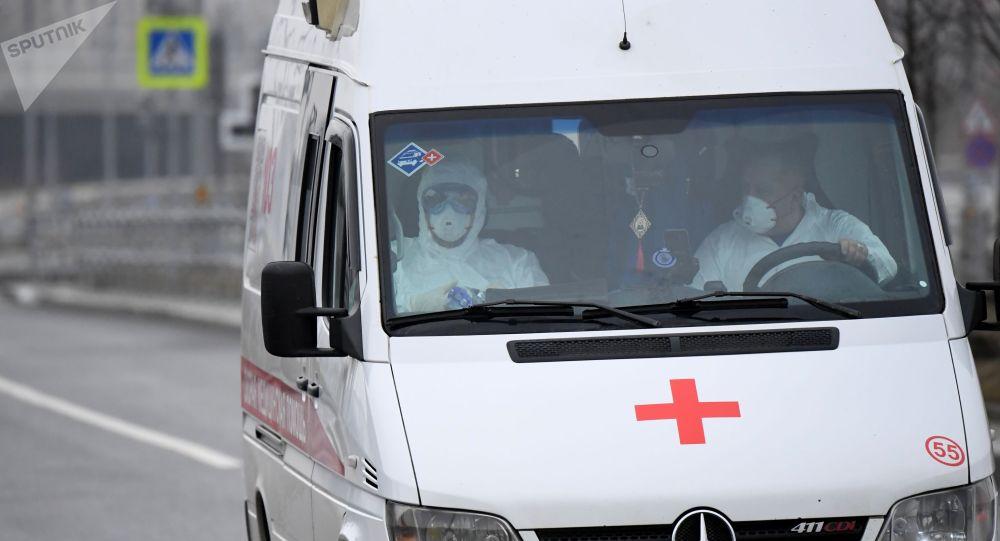 Медицинские работники в защитных костюмах в машине скорой помощи возле территории больничного комплекса в Коммунарке. Больничный комплекс в Коммунарке примет пациентов с подозрением на коронавирус.