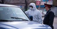 Медсотрудник проверяет температуру водителя на санитарно-карантинном посту на въезде в город Бишкек. Архивное фото