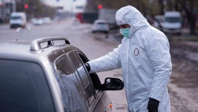Медсотрудник проверяет температуру водителя на санитарно-карантинном блокпосту на въезде в город Бишкек