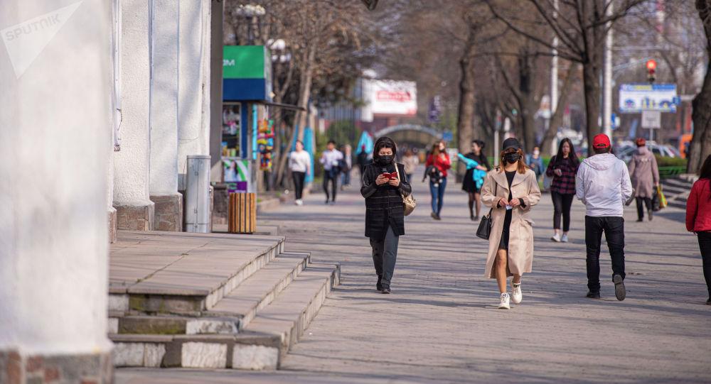 Девушки в медицинских масках на одной из улиц Бишкека