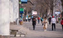 Люди в медицинских масках идут по проспекту Чуй в Бишкеке. Архивное фото