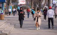 Люди в медицинских масках идут по проспекту Чуй в Бишкеке