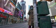 Девушка в медицинской маске на Таймс-сквер в Манхэттене. Архивное фото