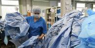 Медкызматкерлерге ылайыкталган коргоочу костюмду ташуу. Архивдик сүрөт