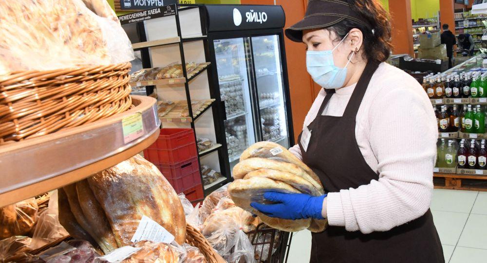 Сотрудница супермакета выкладывает хлеб. Архивное фото