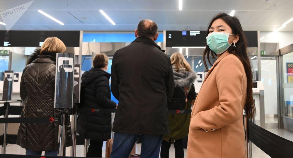 Пассажиры в медицинских масках в зоне регистрации в аэропорту. Архивное фото