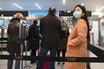 Медициналык беткапчан жүргүнчүлөр аэропорттун каттоо зонасында. Архив