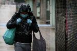 Мужчина в защитной маске идет по улице. Архивное фото
