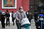 Прохожие в защитных масках на Красной площади в Москве.