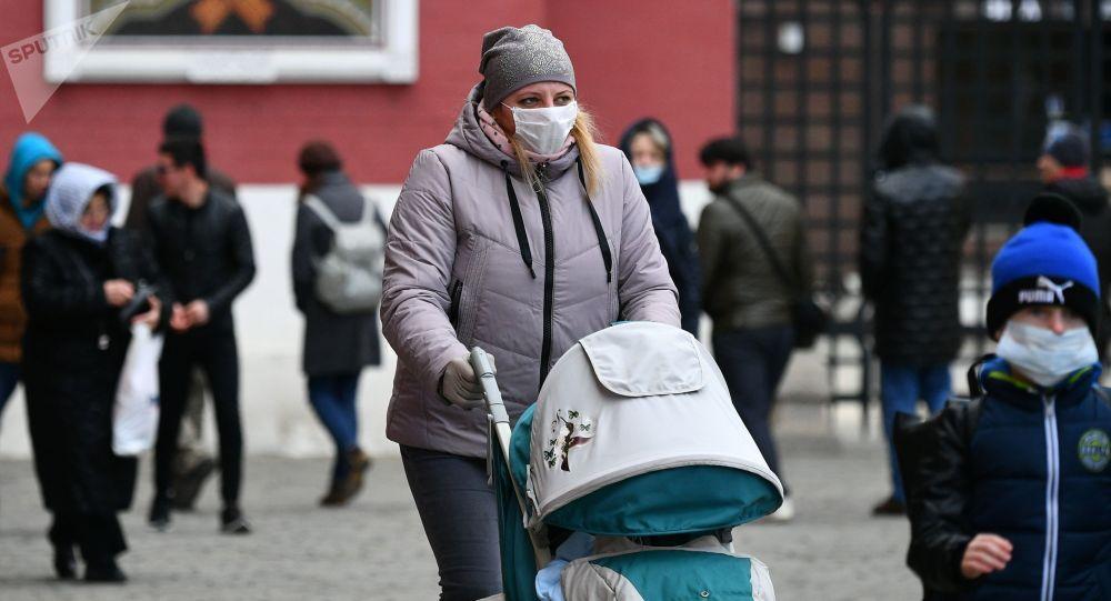 Женщина с коляской в защитной маске. Архивное фото