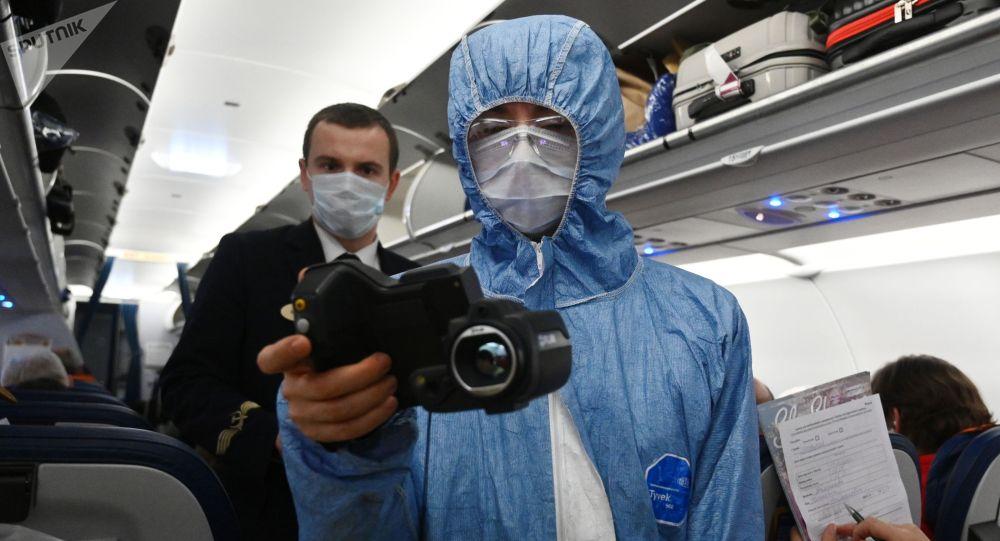 Медицинский сотрудник проверяет тепловизором температуру у пассажиров. Архивное фото