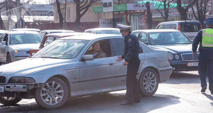 Сотрудник патрульной милиции на оцепленном квадрате между улицами Жукеева-Пудовкина, Ахунбаева, Медерова и набережной в Бишкеке