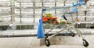 Корзина с продуктами на фоне пустых полок в супермаркете