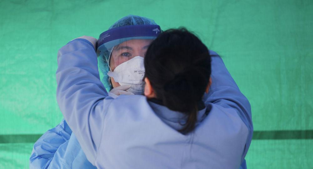 Медицинский работник одевает защитный костюм на площадке для тестирования коронавируса COVID-19 в Сиэтле, США. 26 марта 2020 года