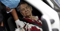 Медицинский работник вакцинирует женщину от гриппа, в соответствии с рекомендациями должностных лиц здравоохранения, чтобы облегчить диагностику коронавируса на фоне вспышки коронавирусной болезни (COVID-19) в Бразилиа. Бразилия, 23 марта 2020 года