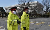 Сотрудники милиции в масках на фоне опасений по поводу распространения коронавируса COVID-19, патрулируют перед зданием парламента в Бишкеке. 26 марта 2020 года