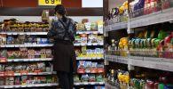Сотрудница торгового зала выкладывает продукцию на полку в супермаркете. Архивное фото