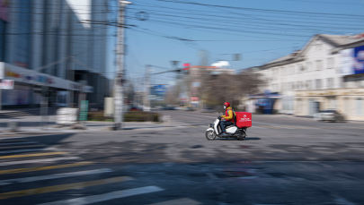 Сотрудник службы доставки едет на мотоцикле, во время режима чрезвычайного положения в Бишкеке из-за ситуации с коронавирусом
