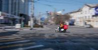 Сотрудник службы доставки едет на мотоцикле. Архивное фото