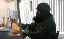 Сотрудник в костюме биозащиты за работой в вирусологической лаборатории, где производится анализ на новую коронавирусную инфекцию.