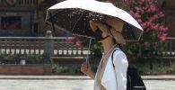Люди в маске используют зонт для защиты от солнца. Архивное фото