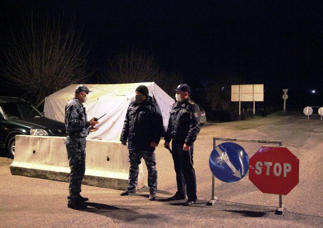 Сотрудники МВД дежурят на блокпосту в городе Ош во время комендантского часа введенного в режиме ЧС в связи с коронавирусом