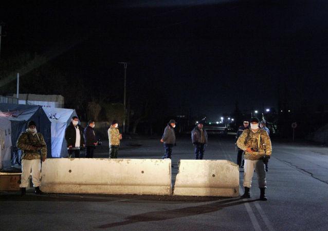 Сотрудник МВД патрулируют на блокпосту в городе Ош во время комендантского часа введенного в режиме ЧС в связи с коронавирусом