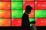 Мужчина в медицинской маске проходит мимо экрана, показывающего показатели на фондовом рынке
