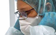Дарыгер медициналык бет капты кийип жатат. Архив