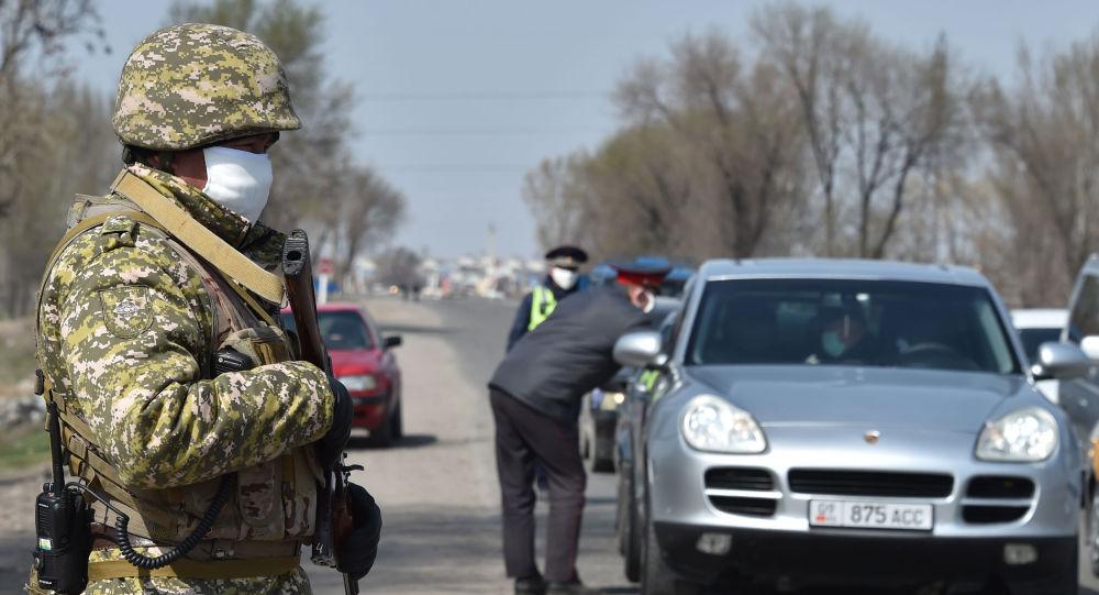 Военнослужащие Национальной гвардии и сотрудники патрульной милиции в лицевых масках видны на контрольно-пропускном пункте, установленном для блокировки города с целью предотвращения распространения коронавирусной болезни COVID-19 на окраине Бишкека. 26 марта 2020 года