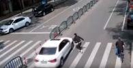 В Китае ребенок избежал смерти под колесами автомобиля благодаря реакции отца.