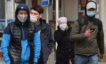 Прохожие в медицинских масках на одой из улиц Бишкека. Архивное фото