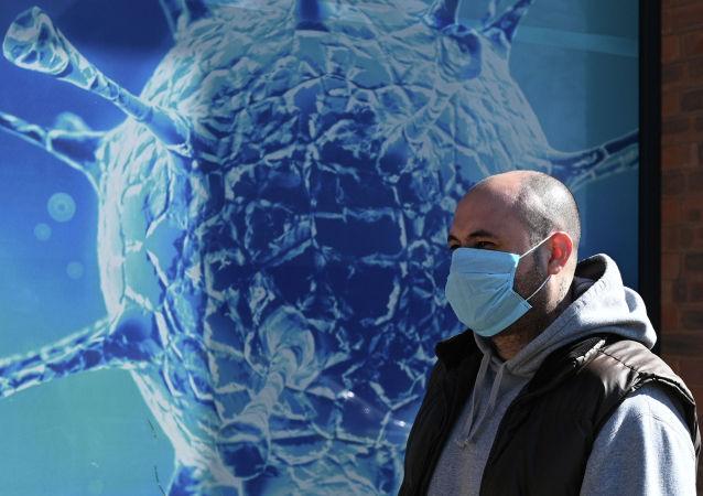 Человек в маске проходит мимо Регионального научного центра в Олдеме, Ланкашир, 26 марта 2020 года