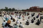 Люди сидят на земле в кругах, нарисованных мелом, чтобы поддерживать безопасную дистанцию, ожидая получения мешков с с продуктами в распределительном пункте благотворительной организации. Карачи, Пакистан, 29 марта 2020 год