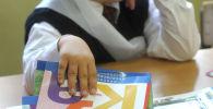 Первоклассник на школьном уроке. Архивное фото