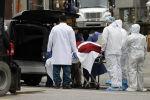Рабочие загружают тело умершего человека в автомобиль-катафалк возле Бруклинского больничного центра во время вспышки коронавирусной болезни (COVID-19) в Бруклинском районе Нью-Йорка. Архивное фото