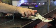 Клиент забирает банкноты в долларах США в банке. Архивное фото