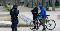 Велосипедчен адамдын документтерин текшерип жаткан полиция кызматкерлери. Архив