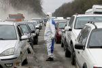 Медицинский работник в защитном снаряжении на контрольно-пропускном пункте за пределами Бишкека