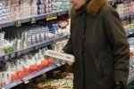 Пожилая женщина выбирает молочную продукцию в супермаркете. Архивное фото