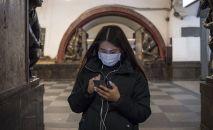 Кыз медициналык бет капчан телефонду карап жатат. Архив