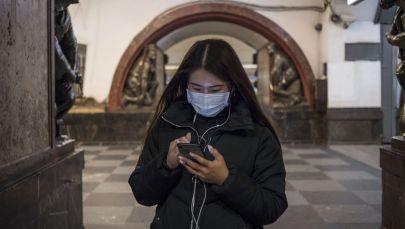Девушка в медицинской маске смотрит в телефон. Архивное фото
