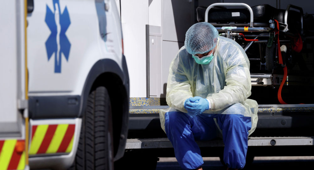 Медицинский работник, носящий защитное снаряжение, делает перерыв во время операций по переносу пациентов. Архивное фото
