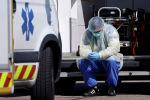 Медицинский работник, носящий защитное снаряжение, делает перерыв во время операций по переносу пациентов, инфицированных коронавирусной болезнью (COVID-19) из Страсбурга в Германию и Швейцарию. Франция, 30 марта 2020 года