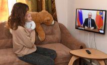 Жительница Симферополя смотрит трансляцию обращения президента РФ Владимира Путина к гражданам.